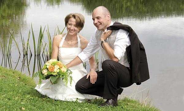 Brautpaar posiert im Grünen am See