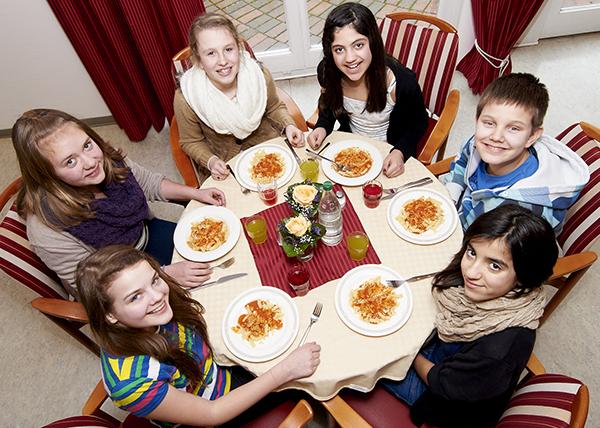 Kinder lächeln beim Essen glücklich in die Kamera