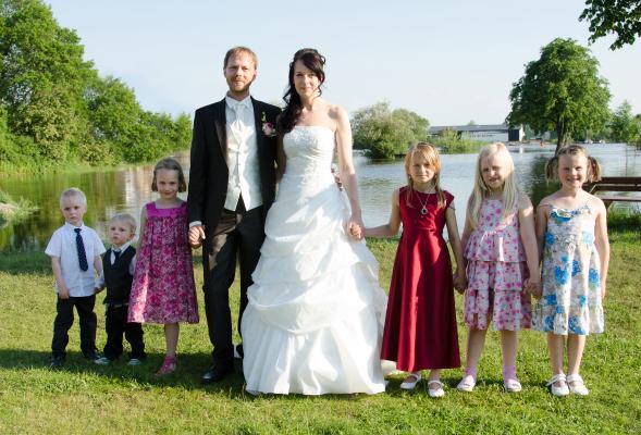 Brautpaar und Blumenmädchen im Grünen
