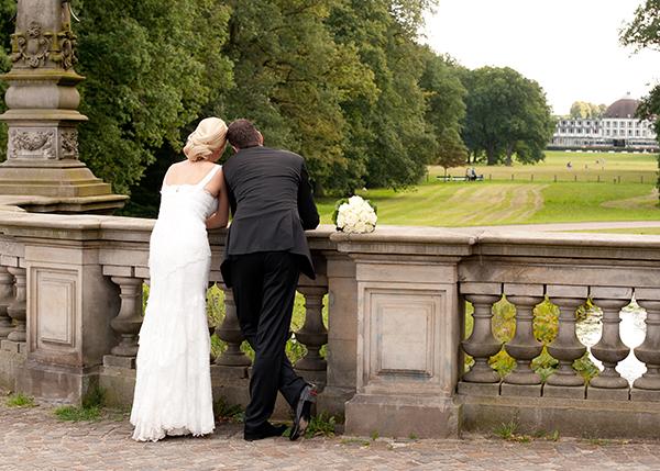 Brautpaar schaut von Brücke in die Ferne