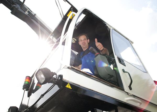 Baggerfahrer hält zum Gruß den Daumen in die Luft