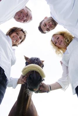 Eine Familie und ein Pferd stehen im Kreis