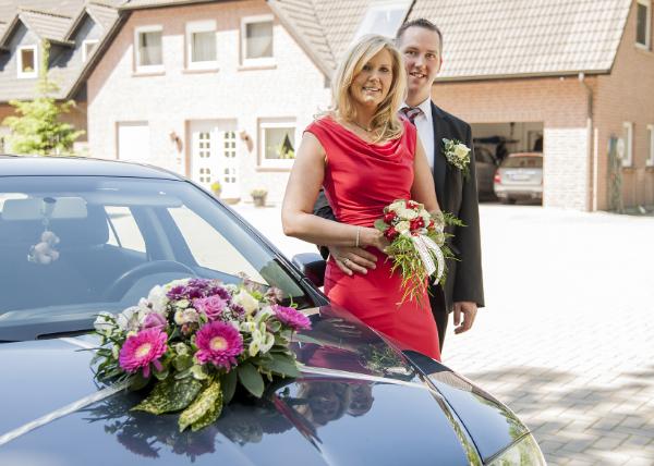 Vor ihren geschmückten Wagen posieren Braut und Bräutigam