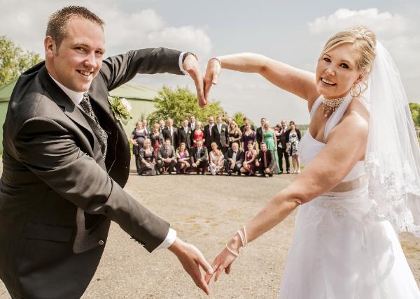Mann und Frau bilden mit ihren Armen ein Herz vor ihren Freunden und Verwandten