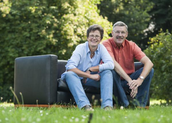 Mann und seine Frau sitzen glücklich auf Couch