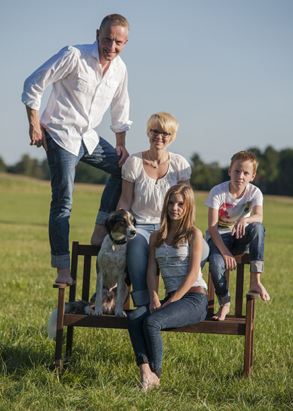 Vater mit seiner Familie und Hund auf Bank