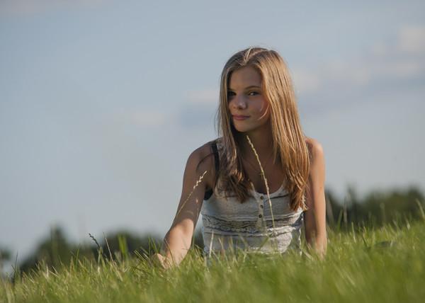 Mädchen sitzt im grünen Gras bei Sonne