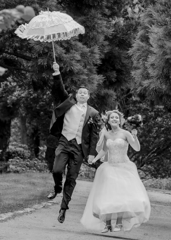 Frisch getrautes Paar läuft auf Kamera zu