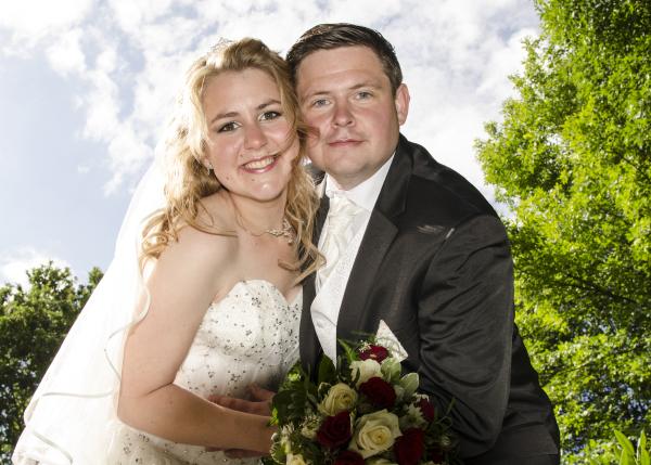 Ein frisch verheiratetes Paar blickt glücklich in die Kamera