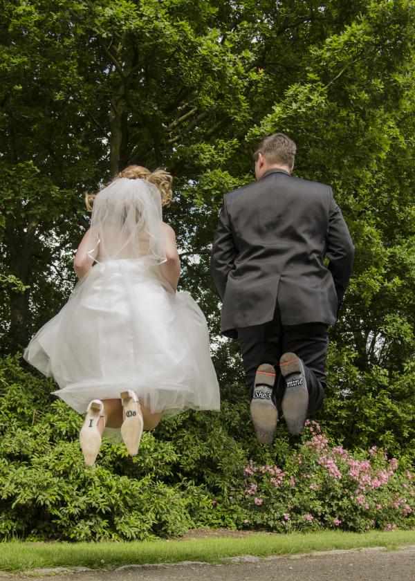 Ein Brautpaar springt vor Freude in die Luft