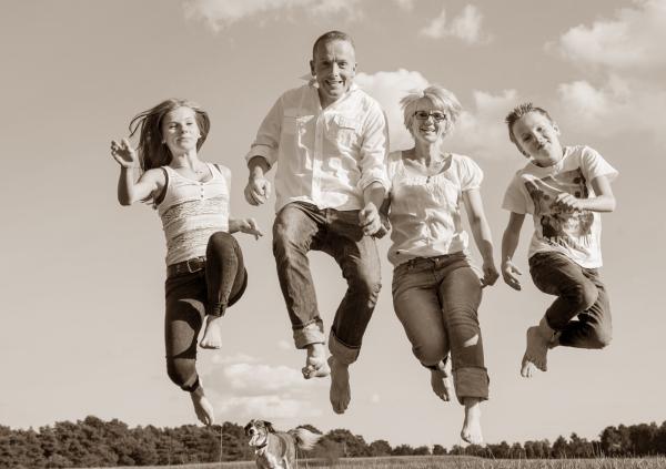Familie springt in die Luft bei schönem Wetter