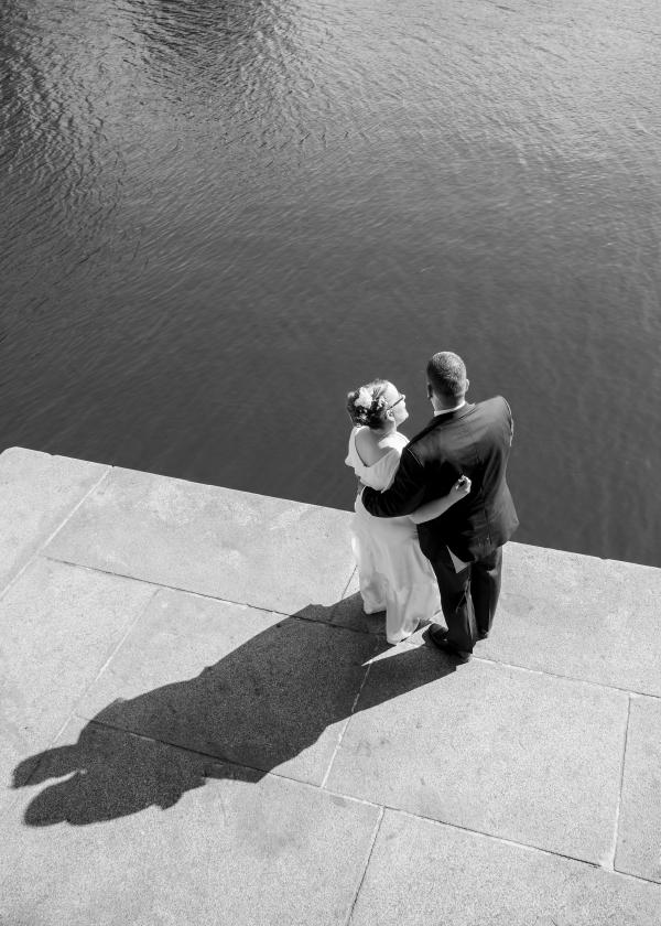 Ein Brautpaar steht an der Alster und blickt nach vorn