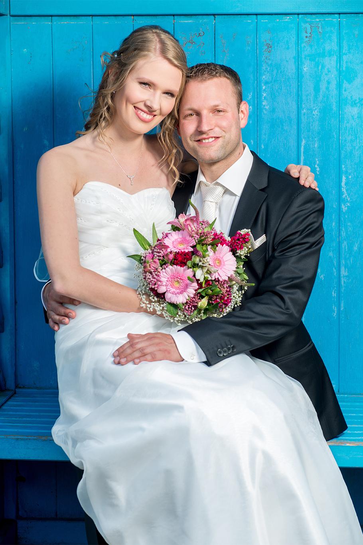 Brautpaar sitzt auf blauer Bank auf ihrer Hochzeit