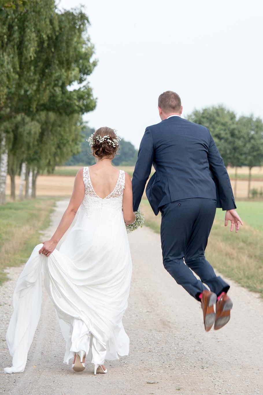 Bräutigam macht Freudensprünge mit seiner Braut an seiner Hochzeit