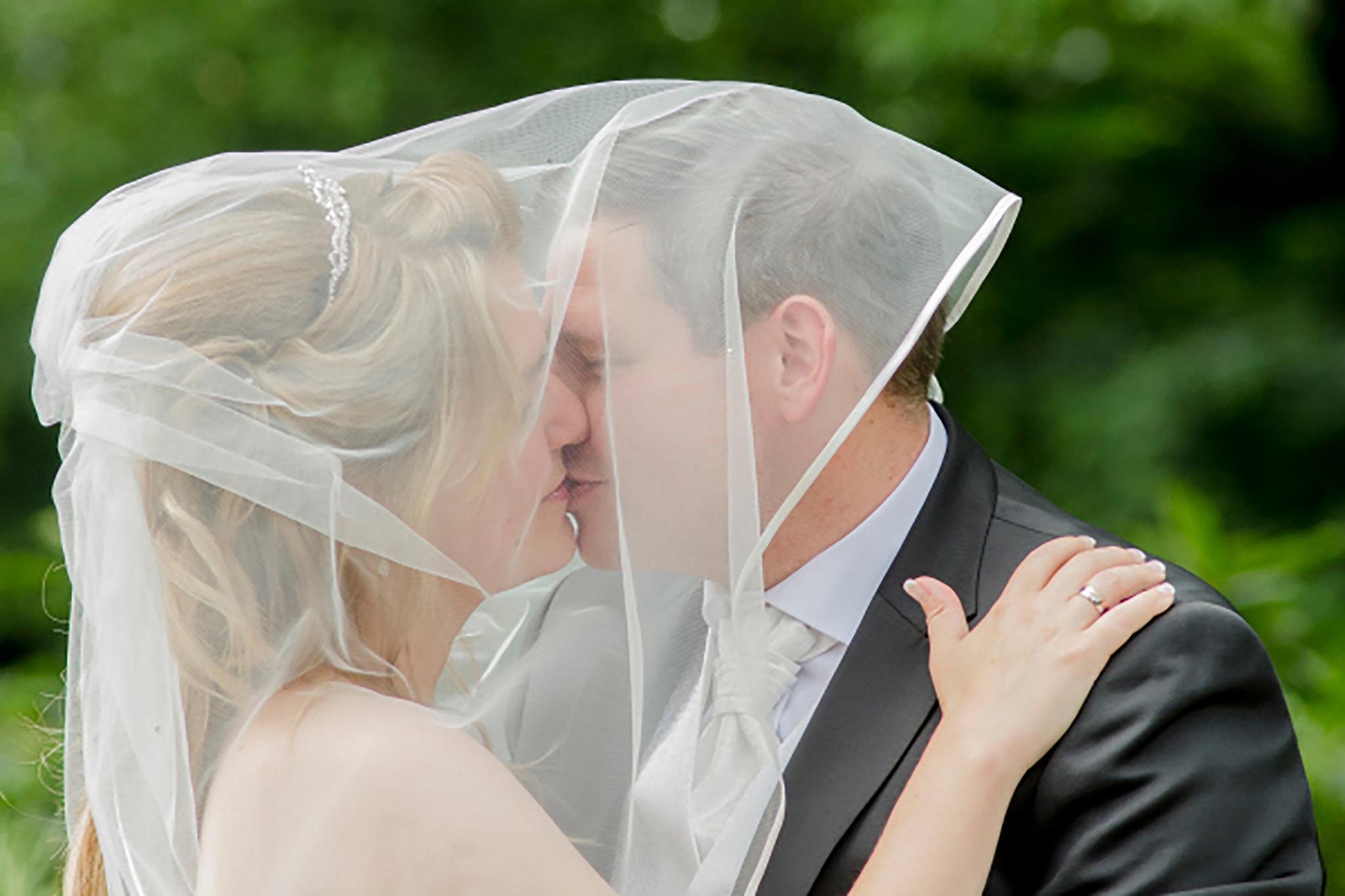 Kuss bei der Hochzeit unter dem Schleier der Braut