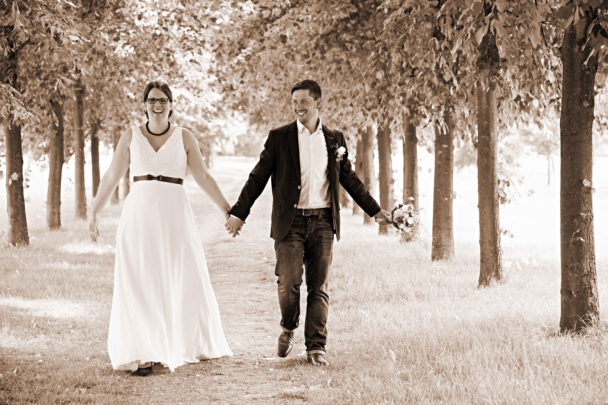 Brautpaar spaziert auf ihrer Hochzeit durch eine Baumallee
