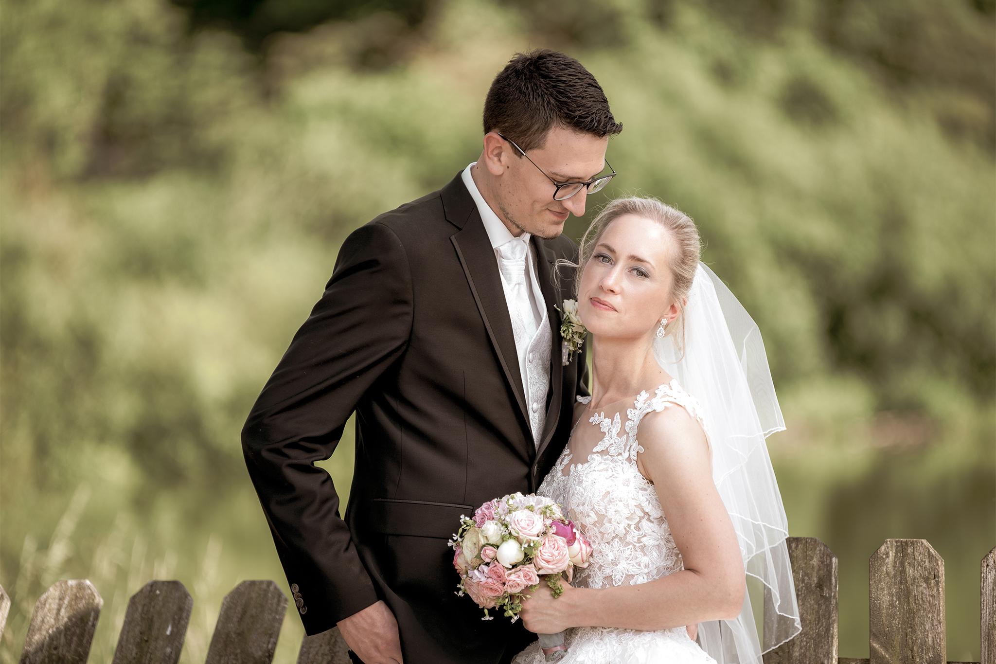 Brautpaar genießt Hochzeit mit Brautstrauß im Grünen