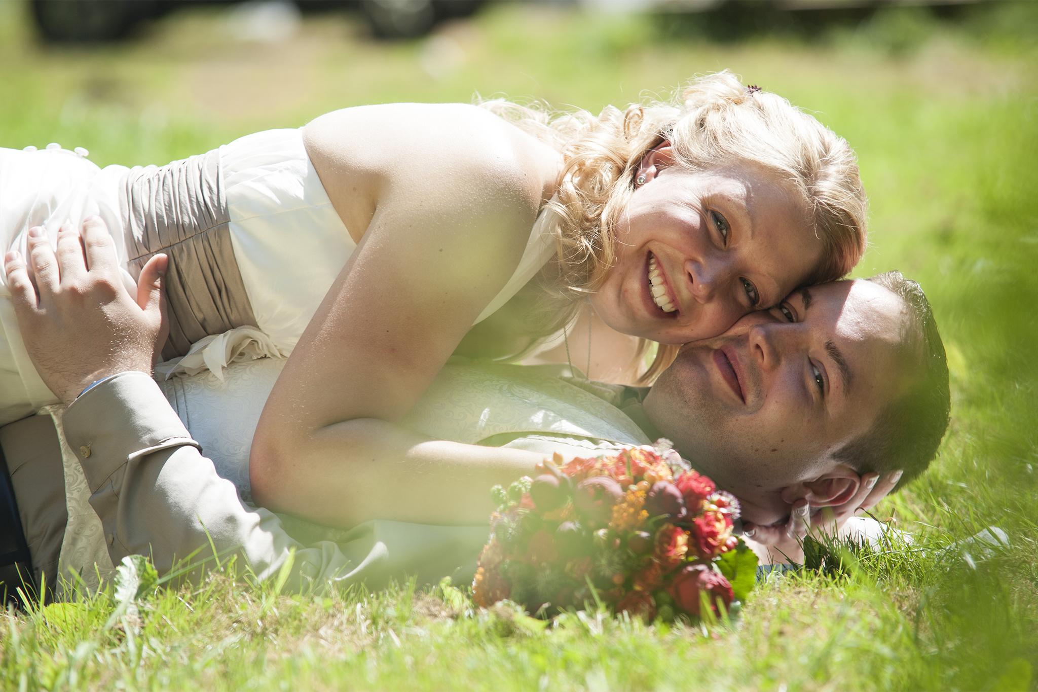 Auf ihrer Hochzeit liegt das glückliches Brautpaar entspannt auf der Wiese