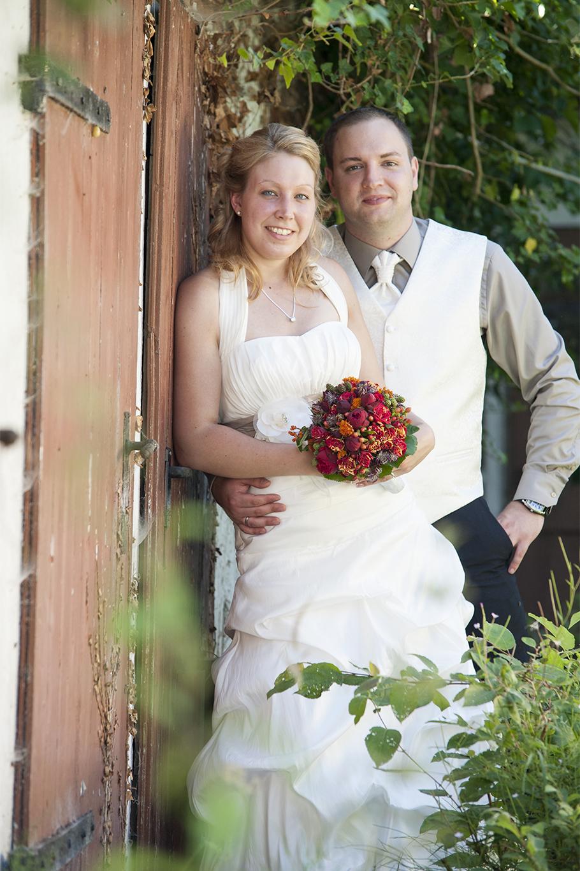 Lässige Braut mit Bräutigam und Blumenstrauß auf der Hochzeit