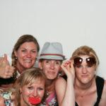 Gruppe mit Requisite schießt Spaßbilder in der Fotobox
