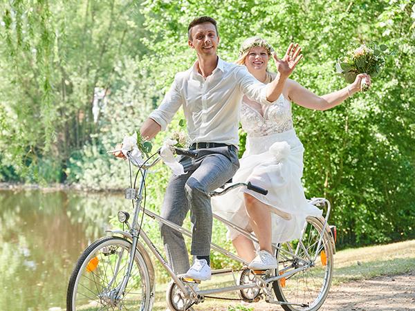 Hochzeitspaar mit Fahrrad am See